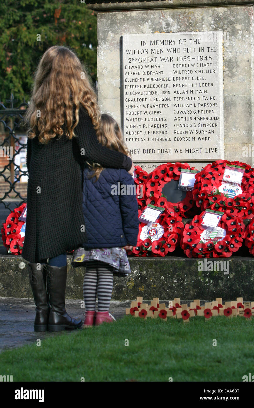 Wilton, Wiltshire, UK. 09th Nov, 2014. Two young girls pay their respects after a Remembrance Day service at the - Stock Image