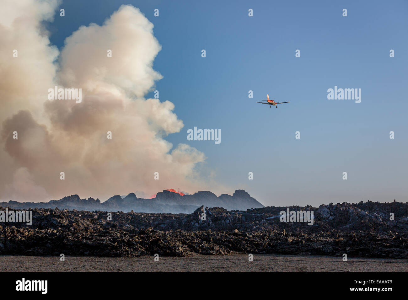 Small plane flying by the volcano eruption at Holuhraun, Bardarbunga Volcano, Iceland - Stock Image