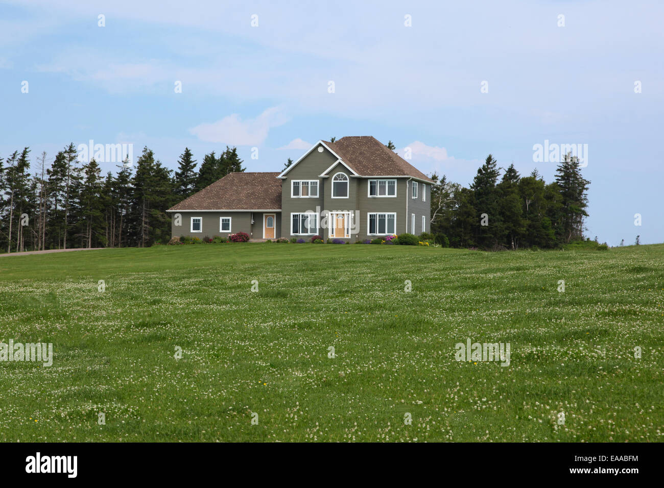 Luxury home with landscaped front yard in Summer - Stock Image