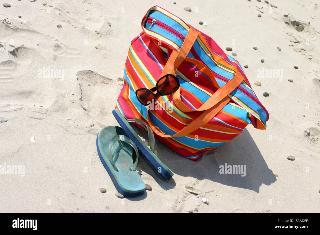 Beach items - flip flops, beach bag and sunglasses lying on the sand - Stock Image