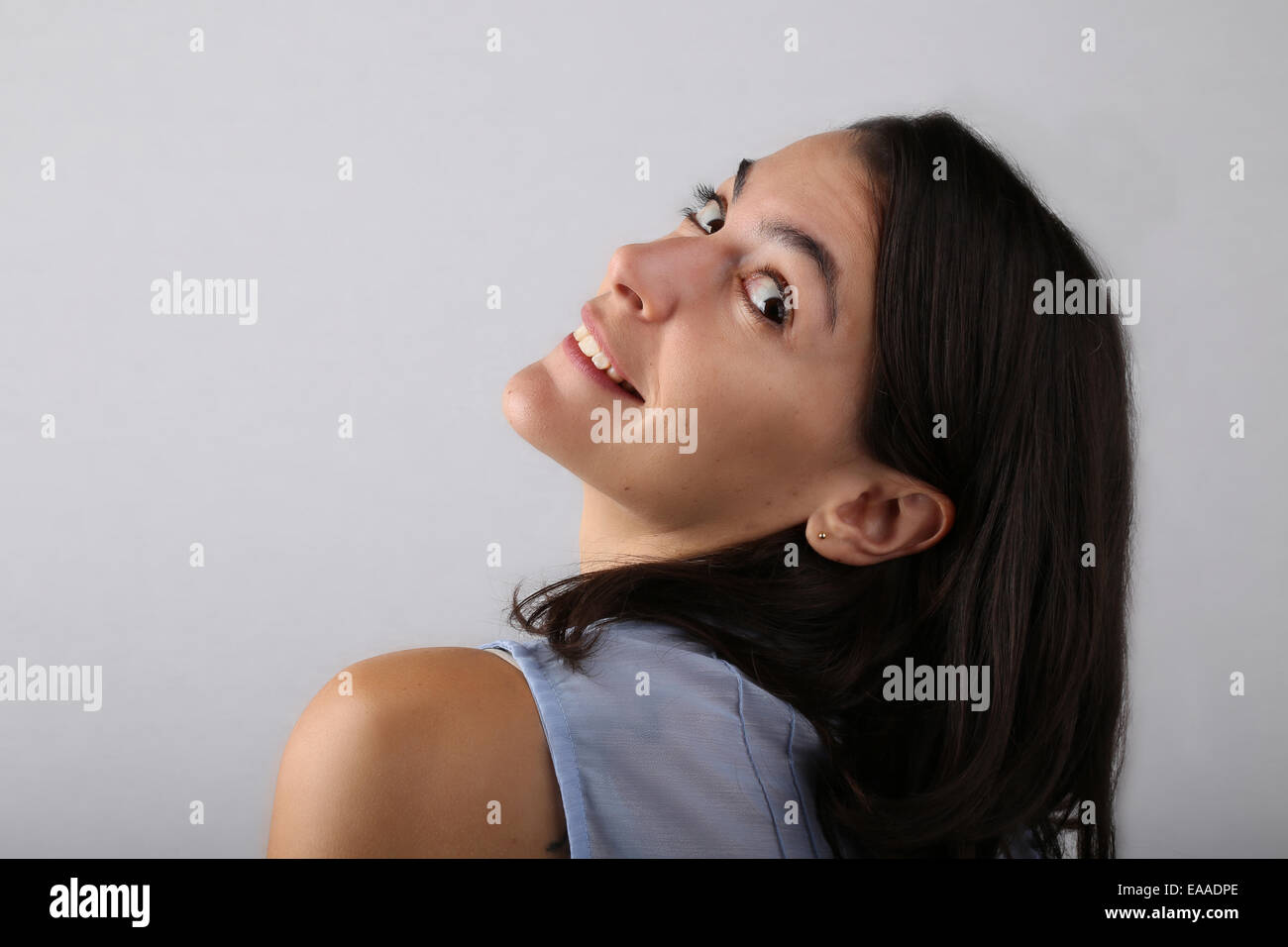 Attractive woman shot from her back leaning her head back toward the camera in a studio - Stock Image