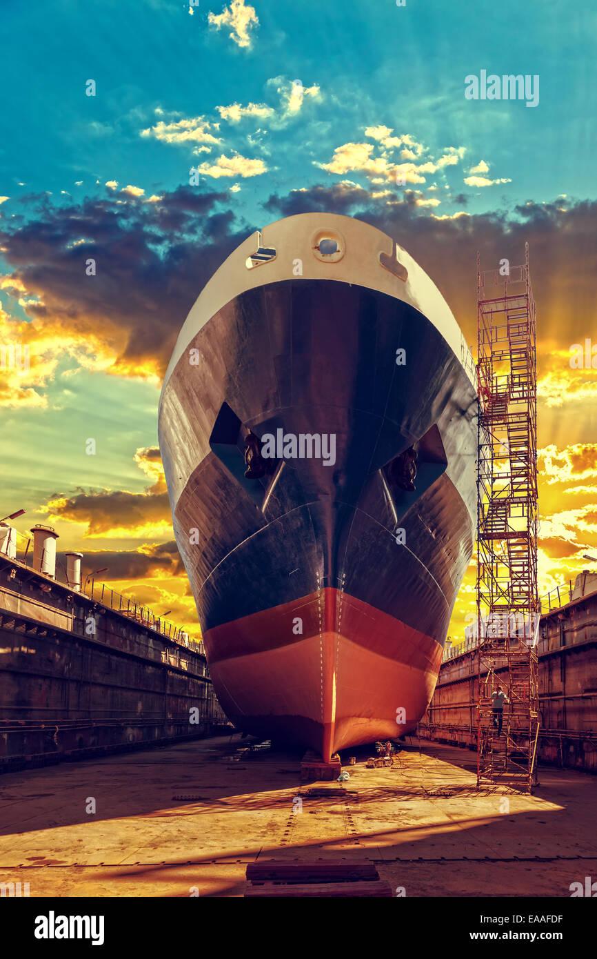 Ship in dry dock at sunrise - shipyard in Gdansk, Poland. - Stock Image
