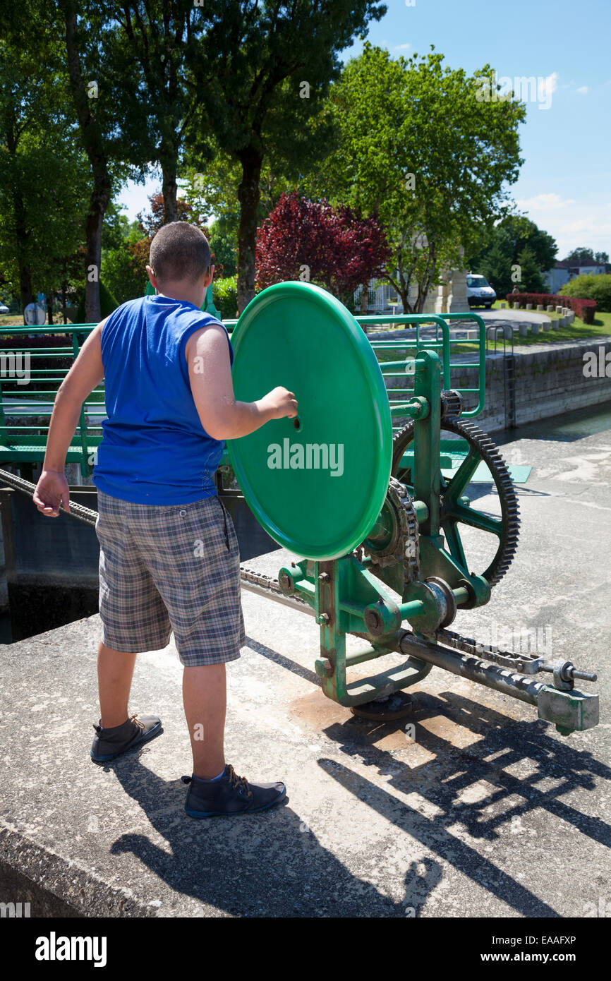 A boy operating the lock gate opening wheel mechanism on the river charente at Jarnac - Stock Image