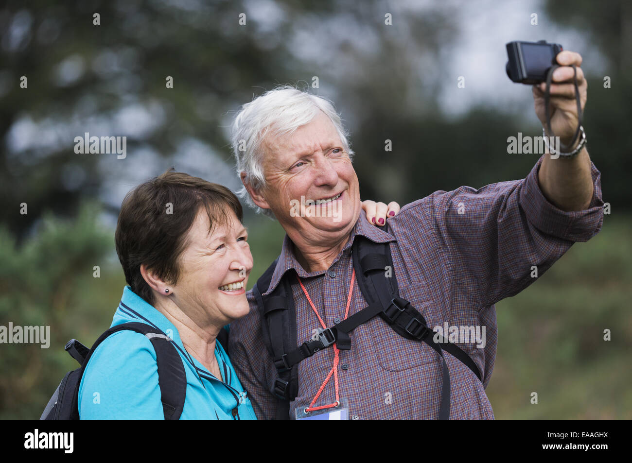 A mature couple taking a selfy photograph while out walking. - Stock Image