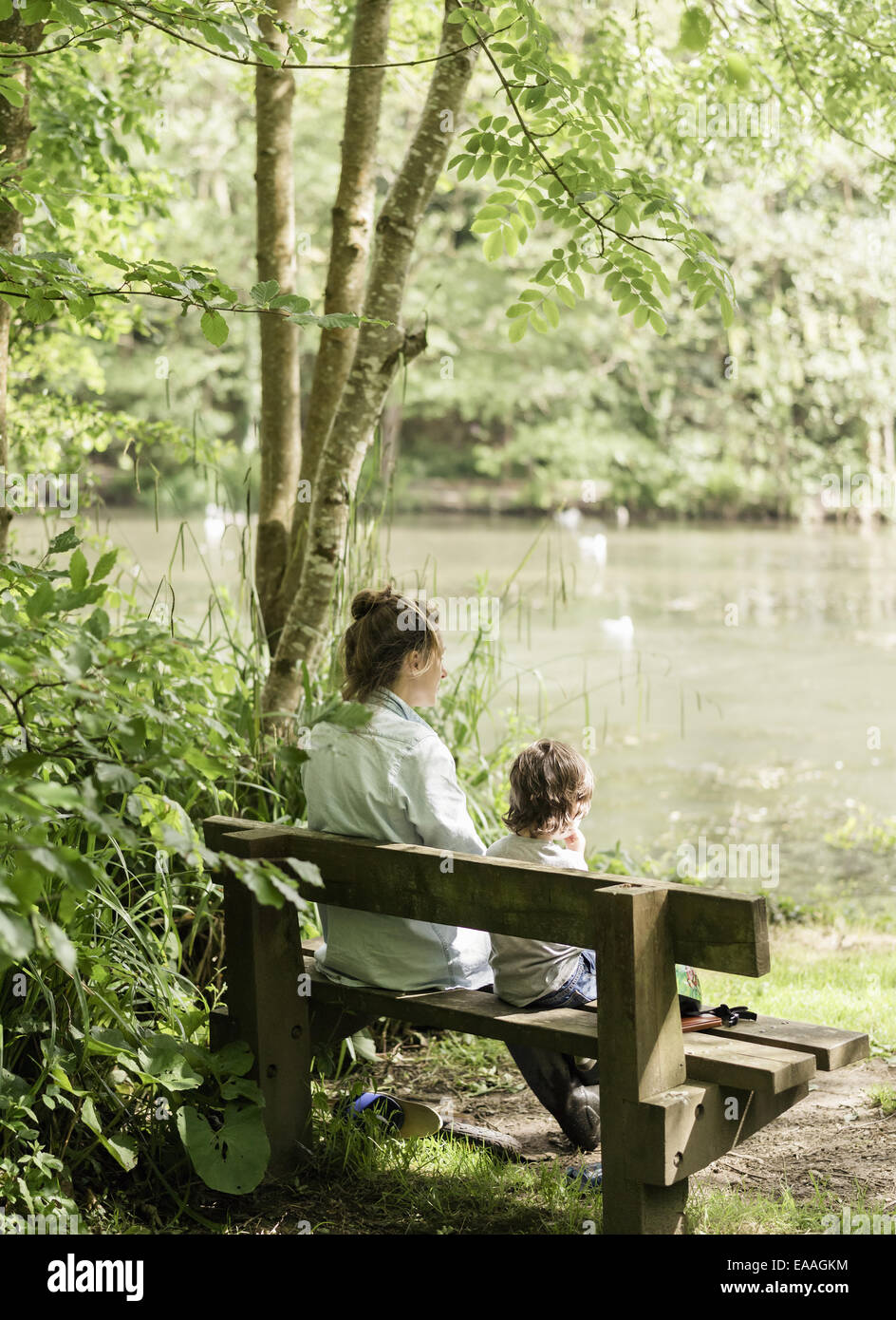 Woman and child sitting on a bench. - Stock Image