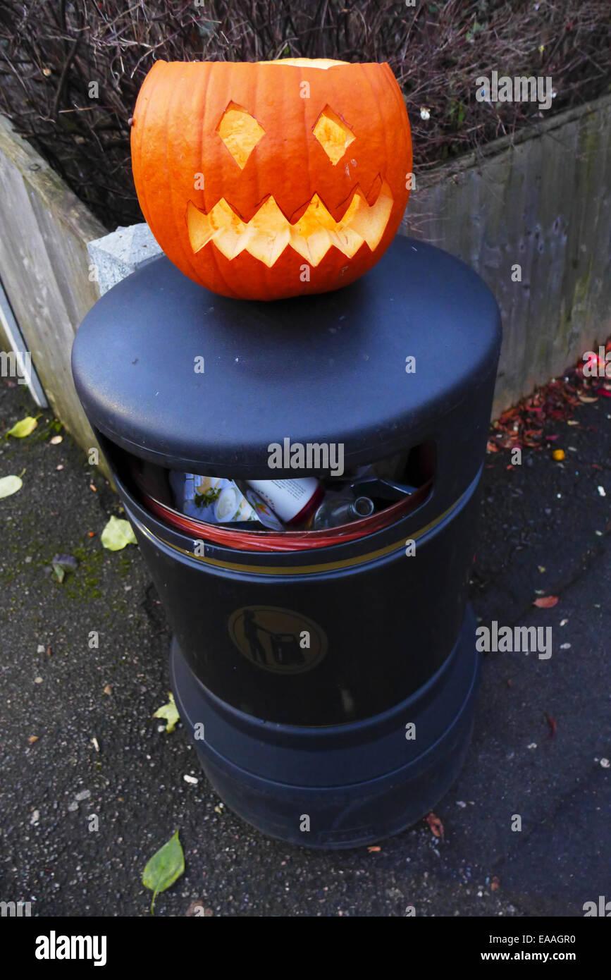A pumpkin discarded after Halloween on top of a street litter bin. Stock Photo