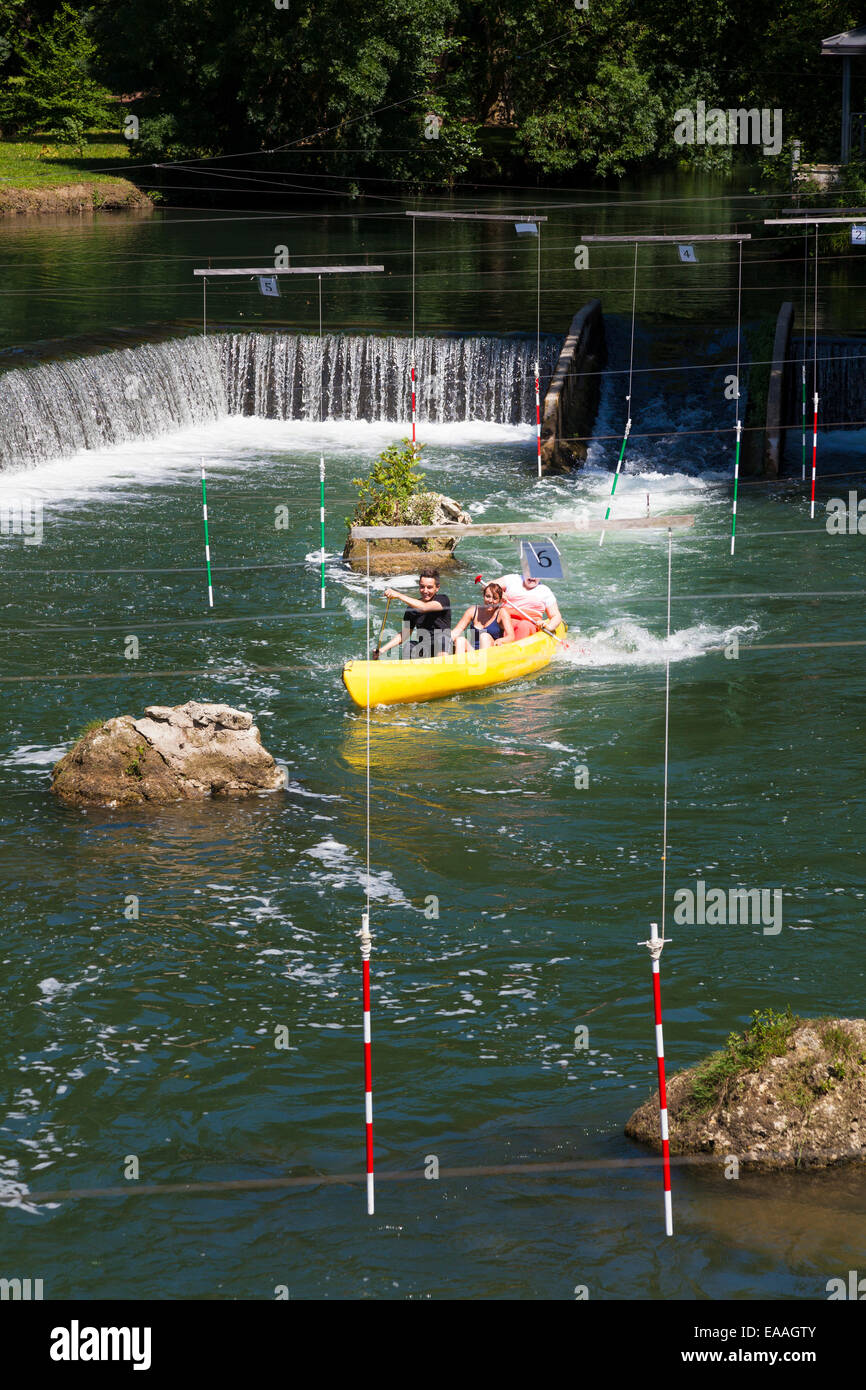 Three people navigate the Canoe slalom course with hanging gates on the river Charente at Jarnac - Stock Image