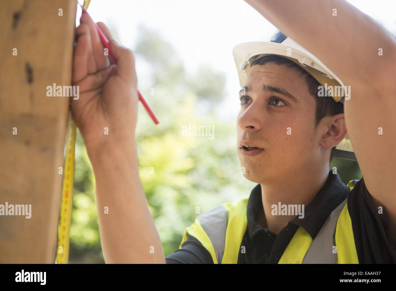 Construction worker wearing high visibility vest and safety helmet. - Stock Image