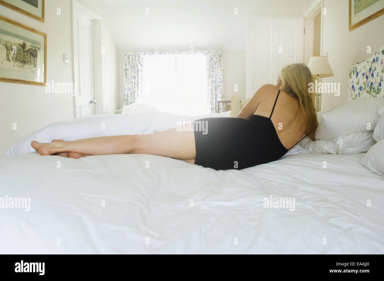 A blonde haired woman lying on her side on a bed. - Stock Image