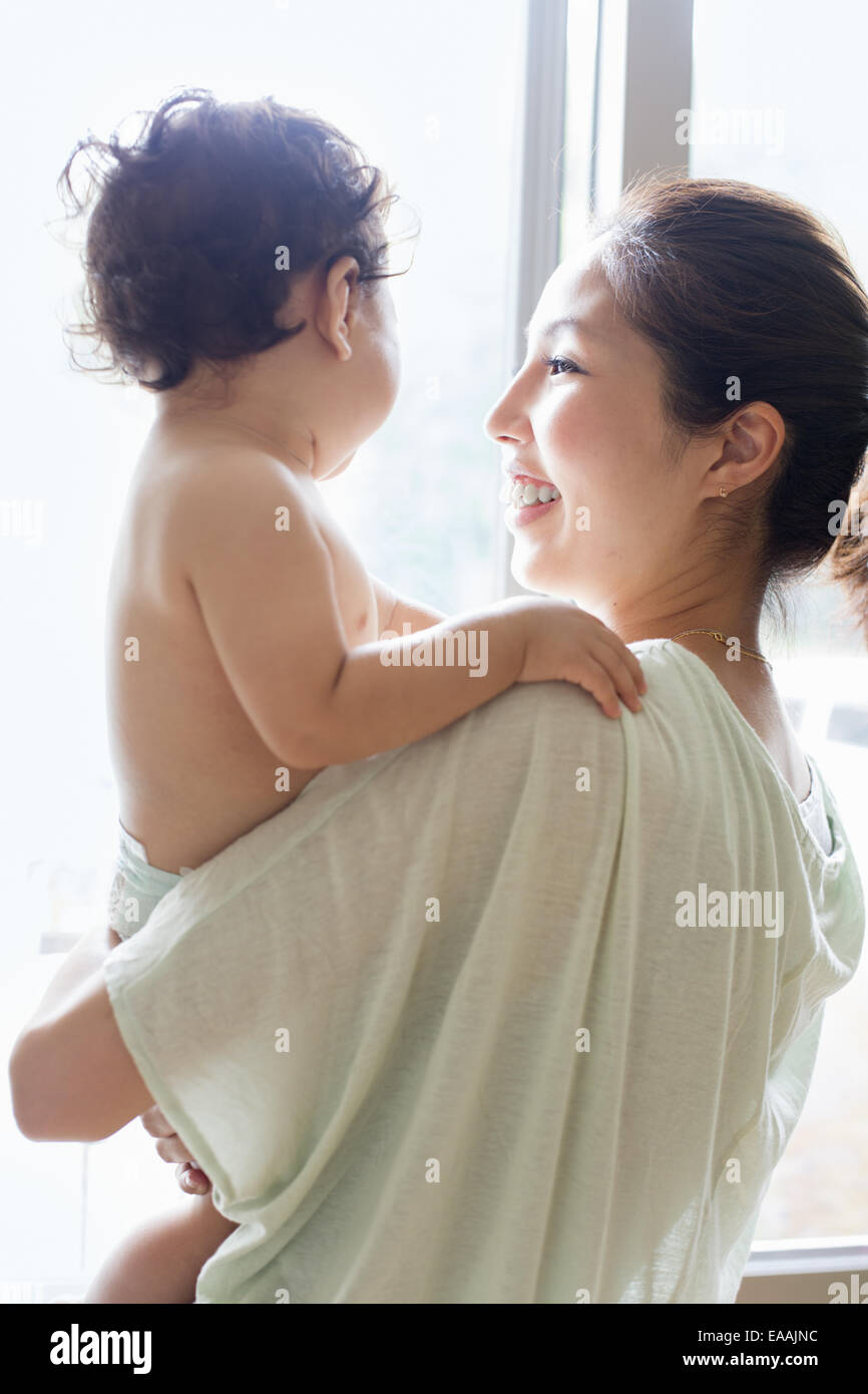 Mother carrying her baby boy. - Stock Image