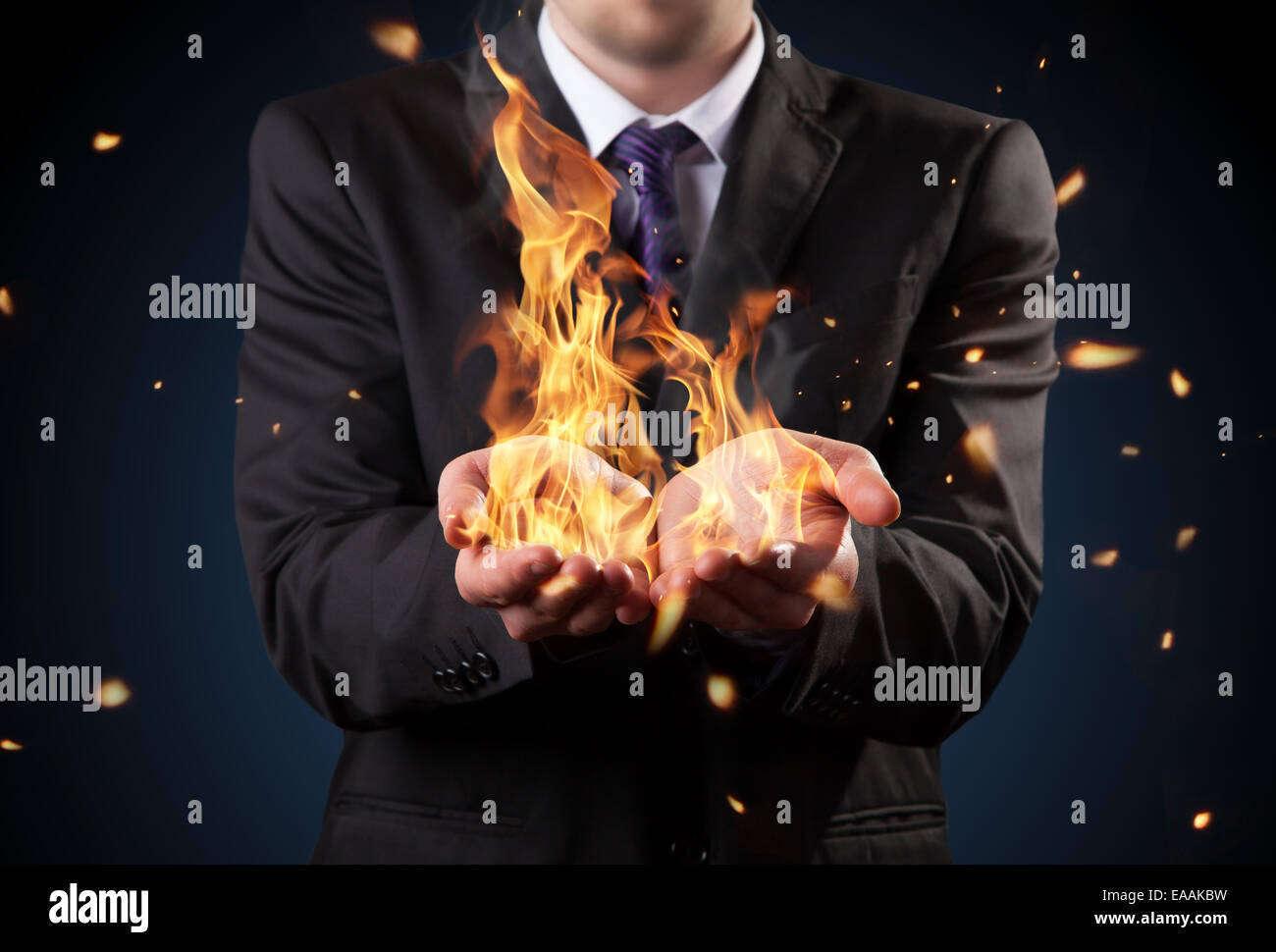 Businessman with fire in hands. Concept of threats and manager responsibility - Stock Image