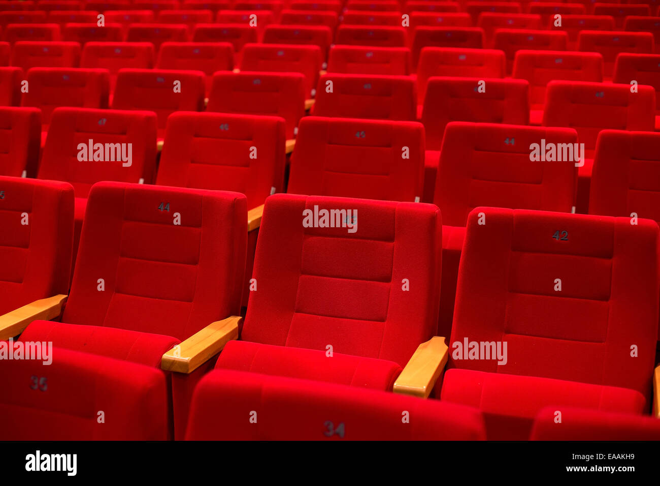 Red and empty theater seats in a row Stock Photo