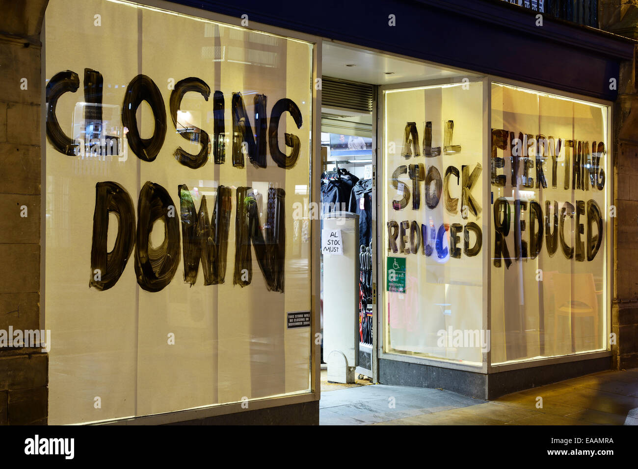 Shop window covered with closing down signs - Stock Image