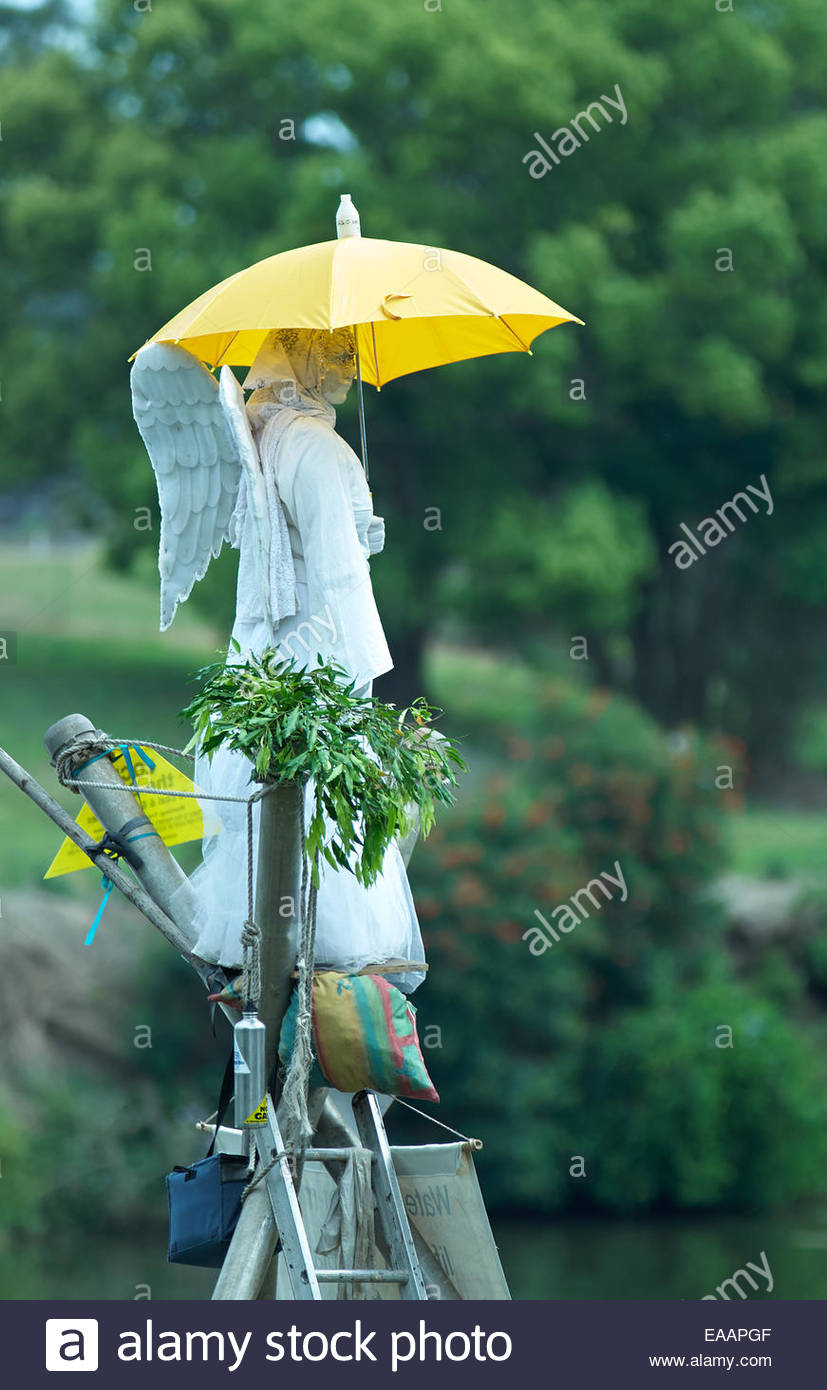The 'earth angel' holding a yellow umbrella, surveys the crowd from a bamboo tripod; at the 'gasfield - Stock Image