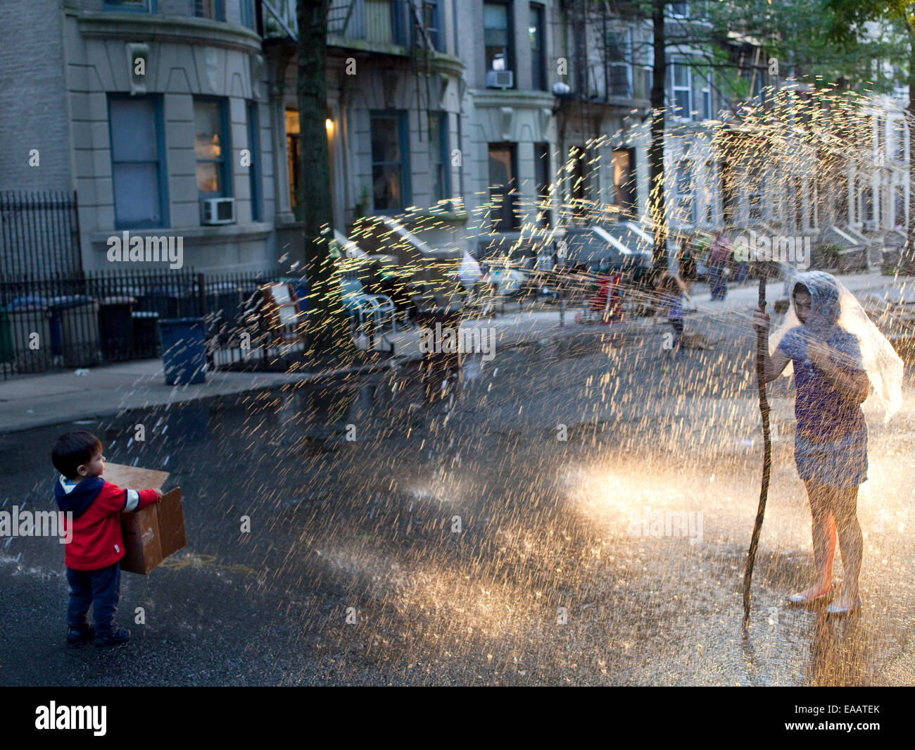kids playing in fire hydrant sprinkler during Brooklyn block party. - Stock Image