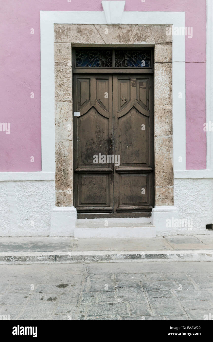 Close Up Of Large Brown Wooden Door With Stone Door Trim On A Pink And White