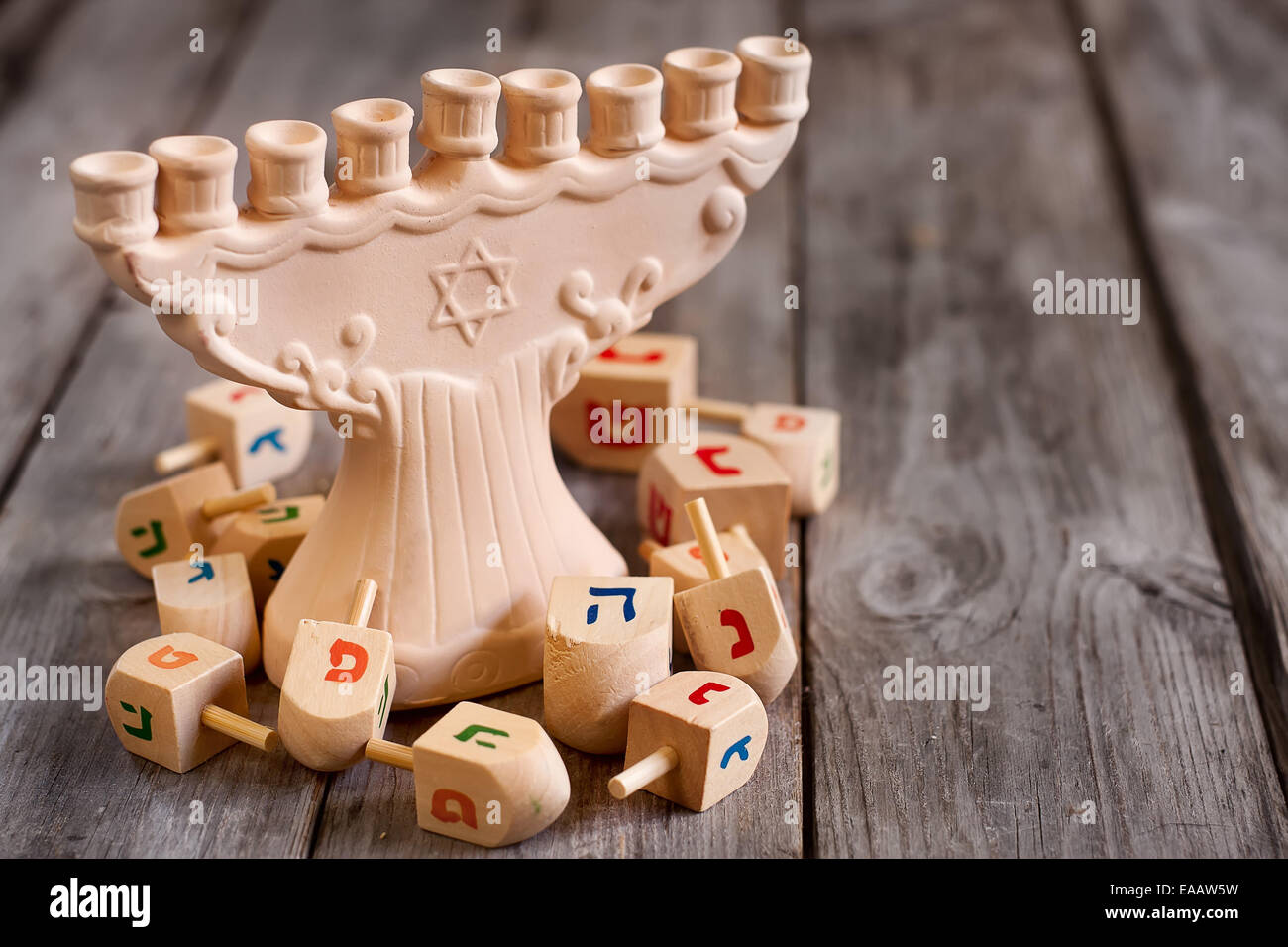 Jewish holiday hannukah symbols - menorah and wooden dreidels. Copy space background. - Stock Image