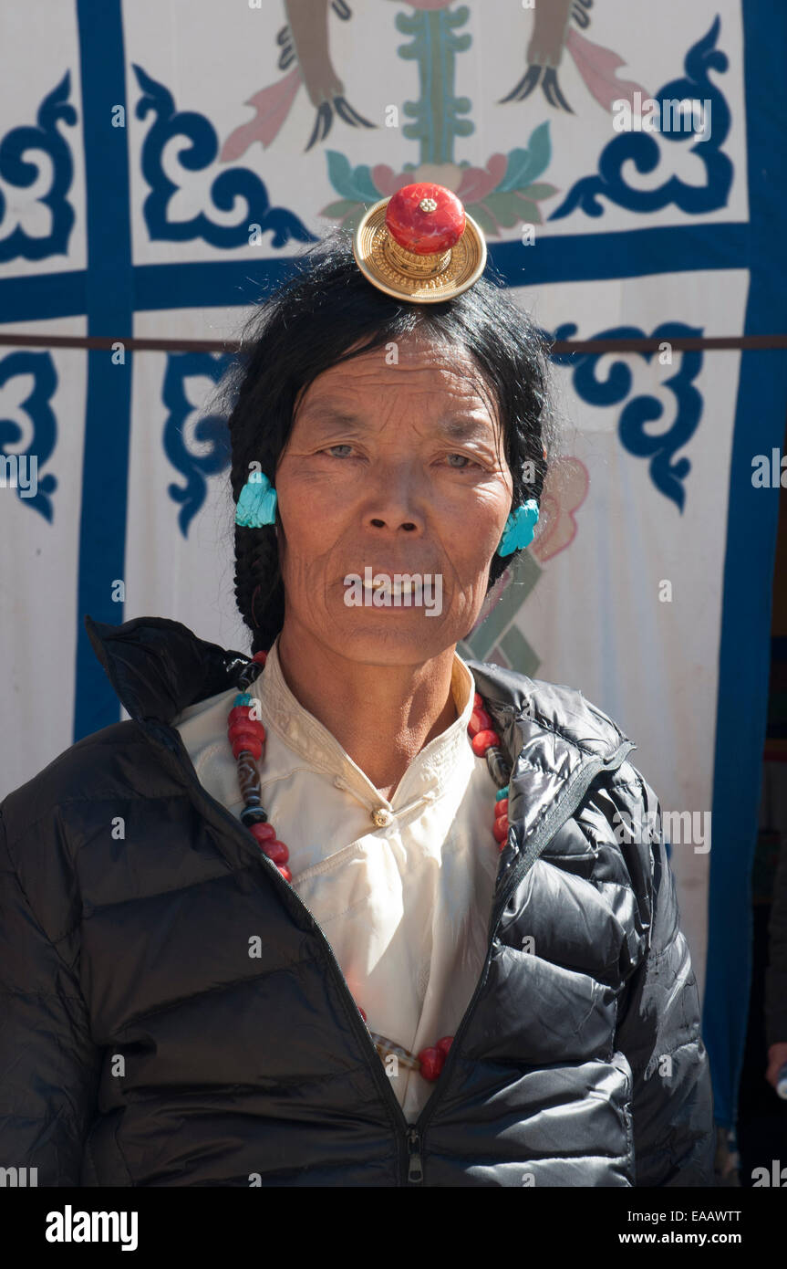 A Tibetan woman wearing traditional jewellery visits the Potala Palace in Lhasa - Stock Image