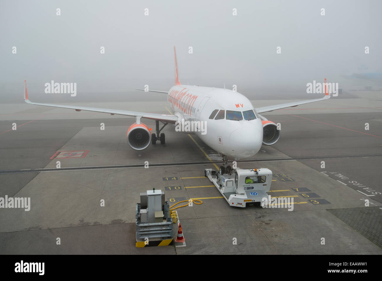 Fog delays an EasyJet Airbus A320 airliner from taking off at Amsterdam Schiphol Airport (Editorial use only). - Stock Image