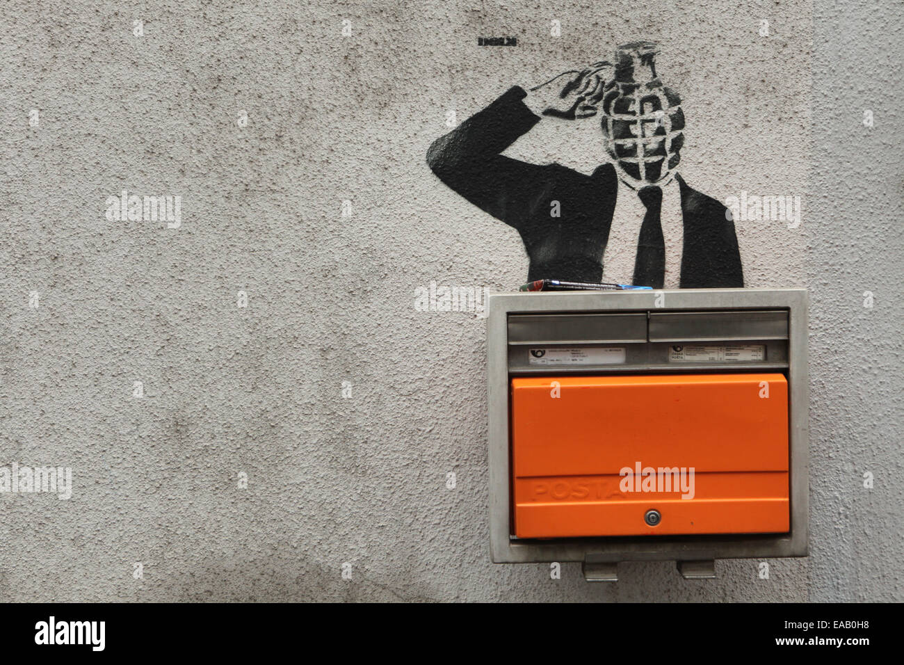 Grenade-headed person blowing his head up depicted in a street graffiti next to a letter box in Prague, Czech Republic. - Stock Image