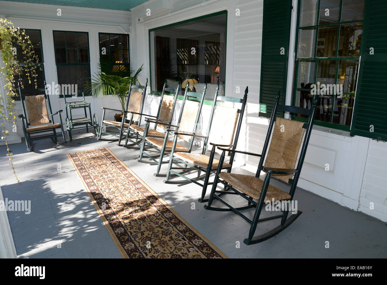 Many Wood And Wicker Rocking Chairs On A Large Outdoor Front Porch