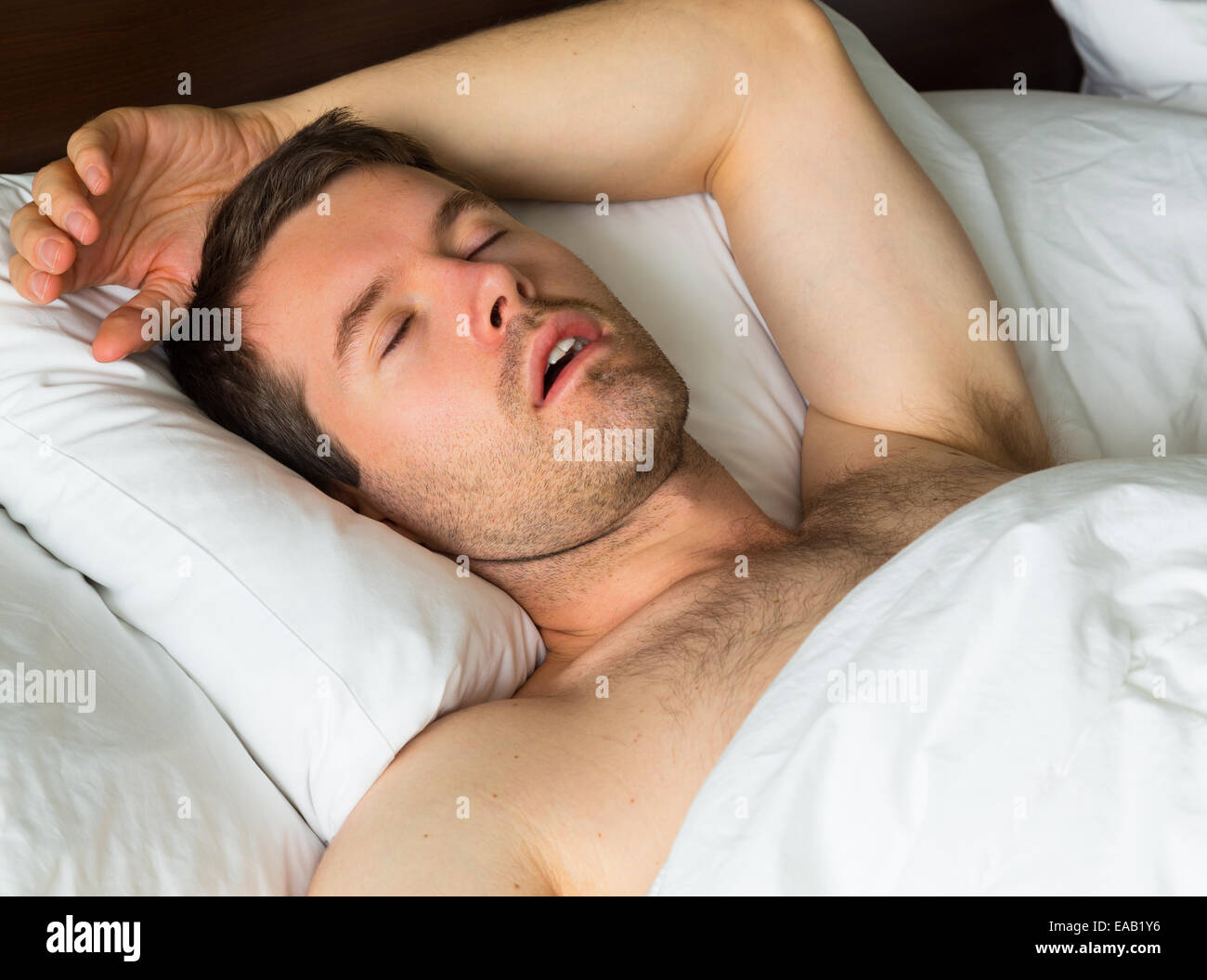 A sleeping man in bed with his arm up - Stock Image