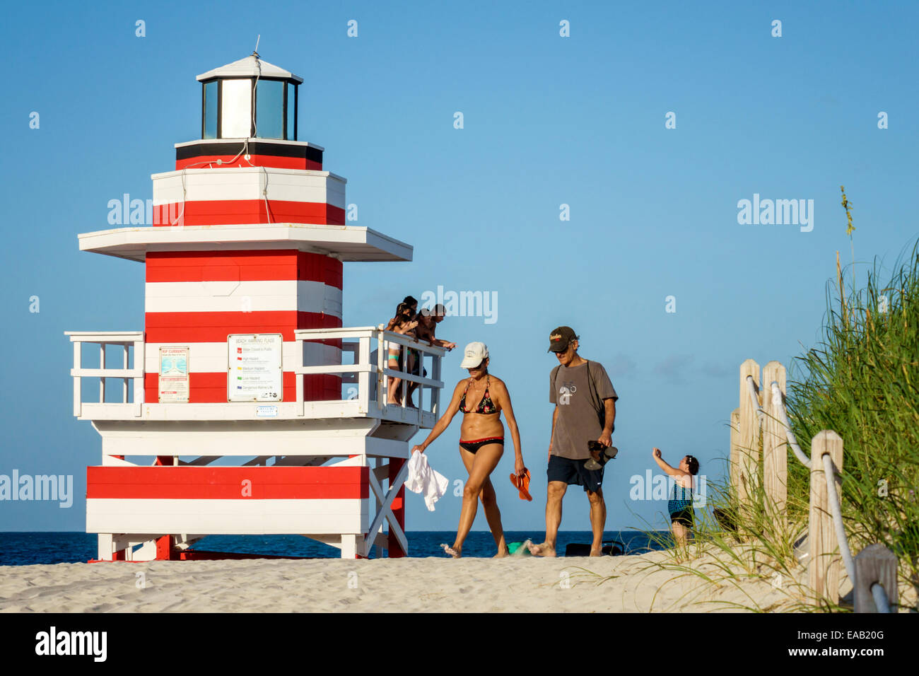Miami Beach Florida sand lighthouse shaped lifeguard station Atlantic Ocean water sand man woman couple sunbathers Stock Photo