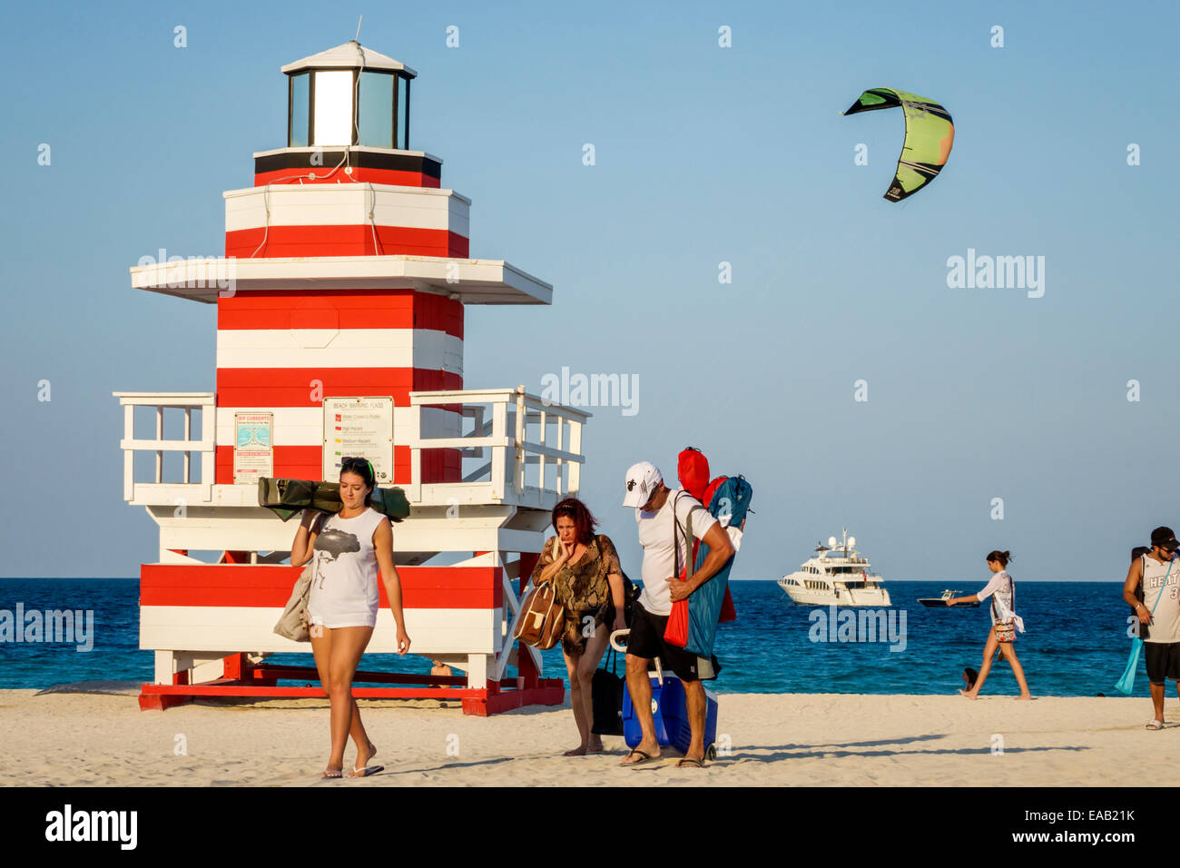 Miami Beach Florida sand lighthouse shaped lifeguard station Atlantic Ocean water sand woman man sunbathers boat Stock Photo