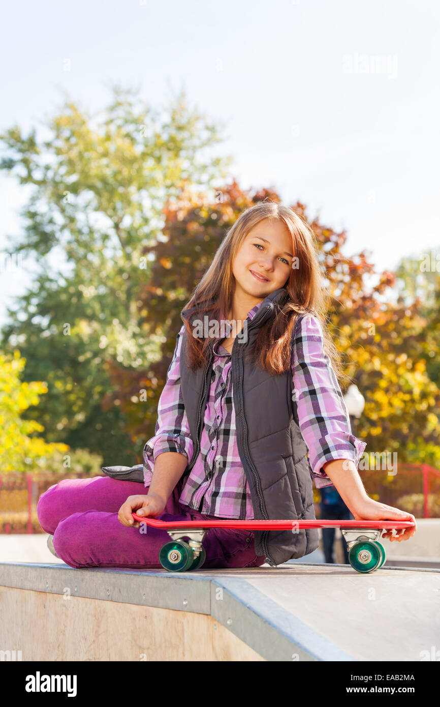 Positive girl holds skateboard sits on ground - Stock Image