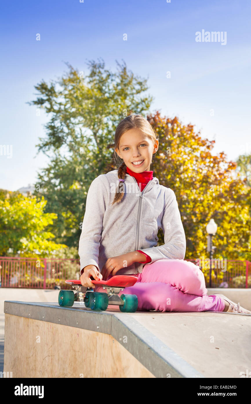 Smiling girl with braid holding red skateboard - Stock Image