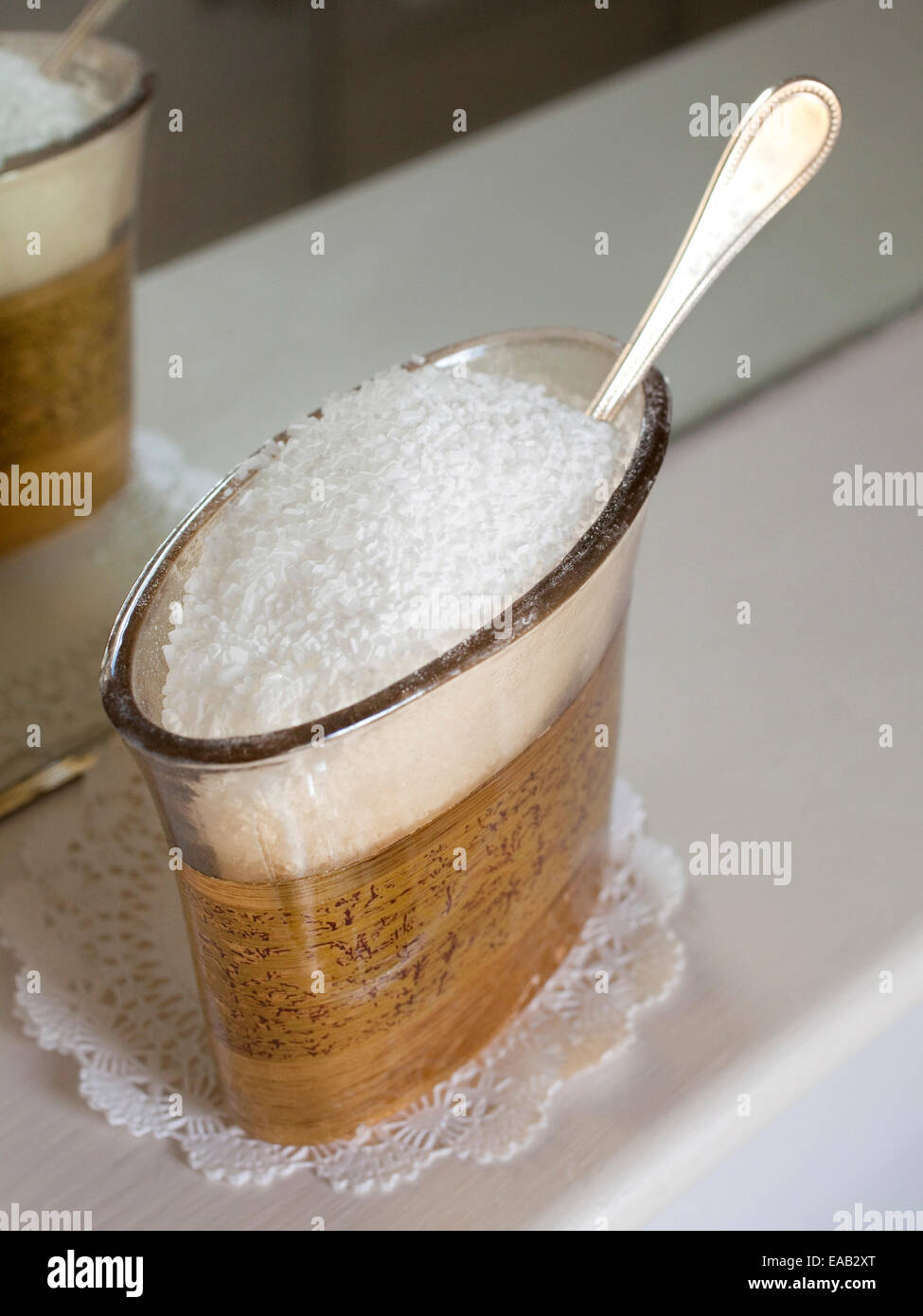 Bath salts and silver spoon in glass container in bathroom. - Stock Image