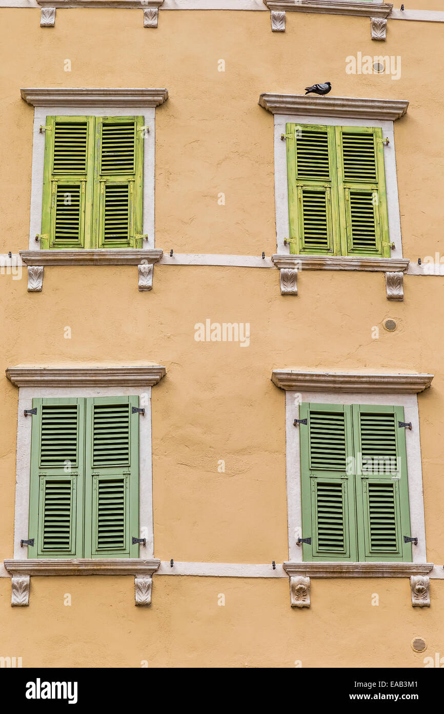Shuttered windows on a colourful building in old town Riva Del Garda - Stock Image