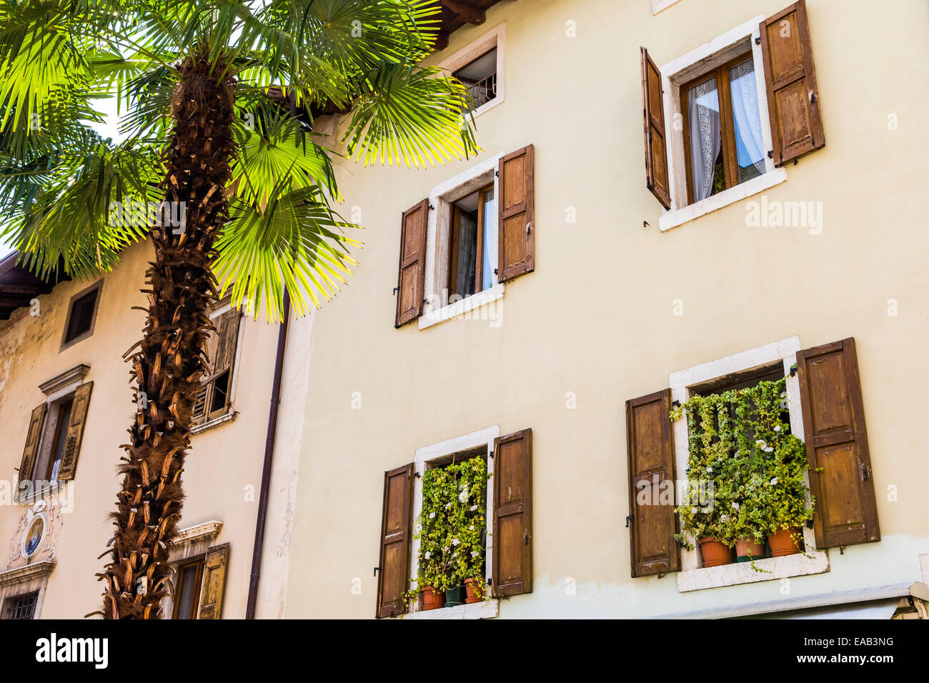 Shuttered windows on a colourful building in Arco, Lake Garda, Trentino, Italy - Stock Image