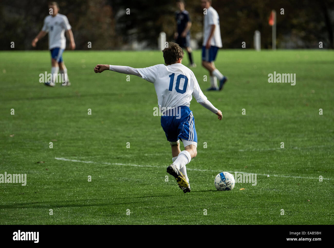 Youth soccer player takes a free kick during a match game. - Stock Image
