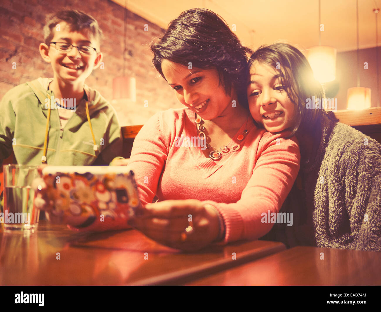 Woman takes picture of self and daughter while son watches - Stock Image