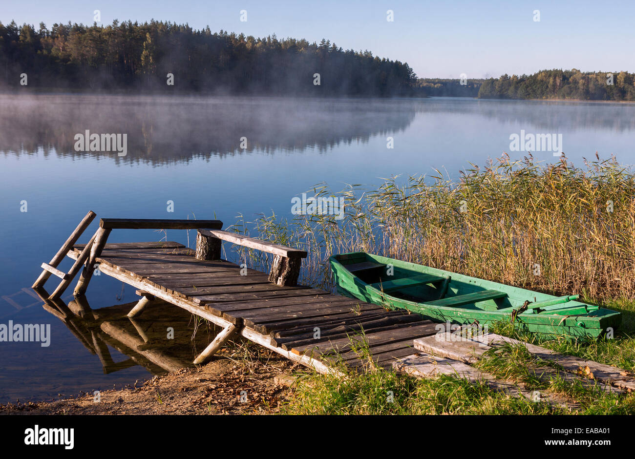 Old wooden fishing boat and old bridge on the foggy lake in morning hour - Stock Image