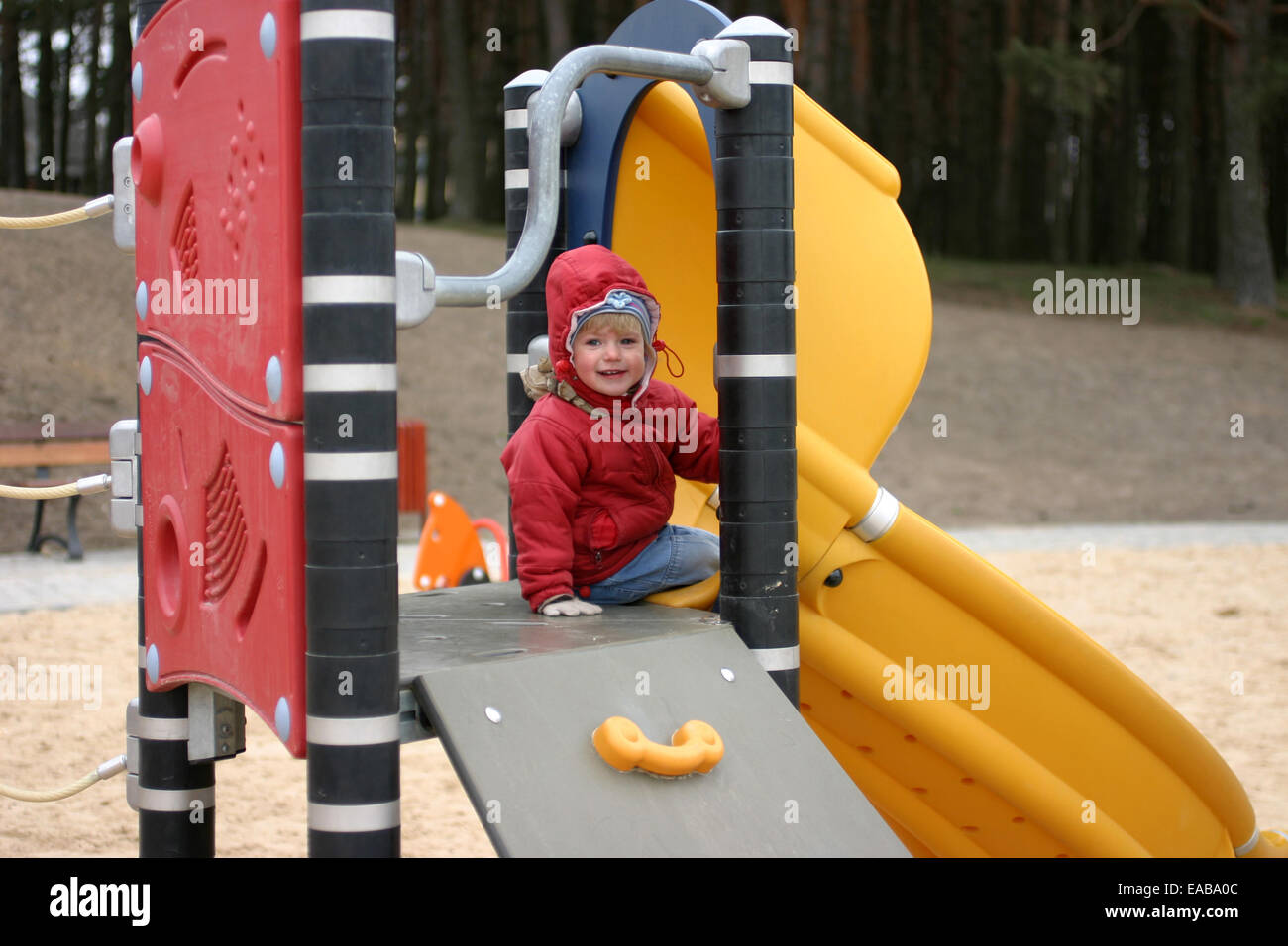 Two years old girl sitting on the jungle gym at cold spring day and smiling - Stock Image