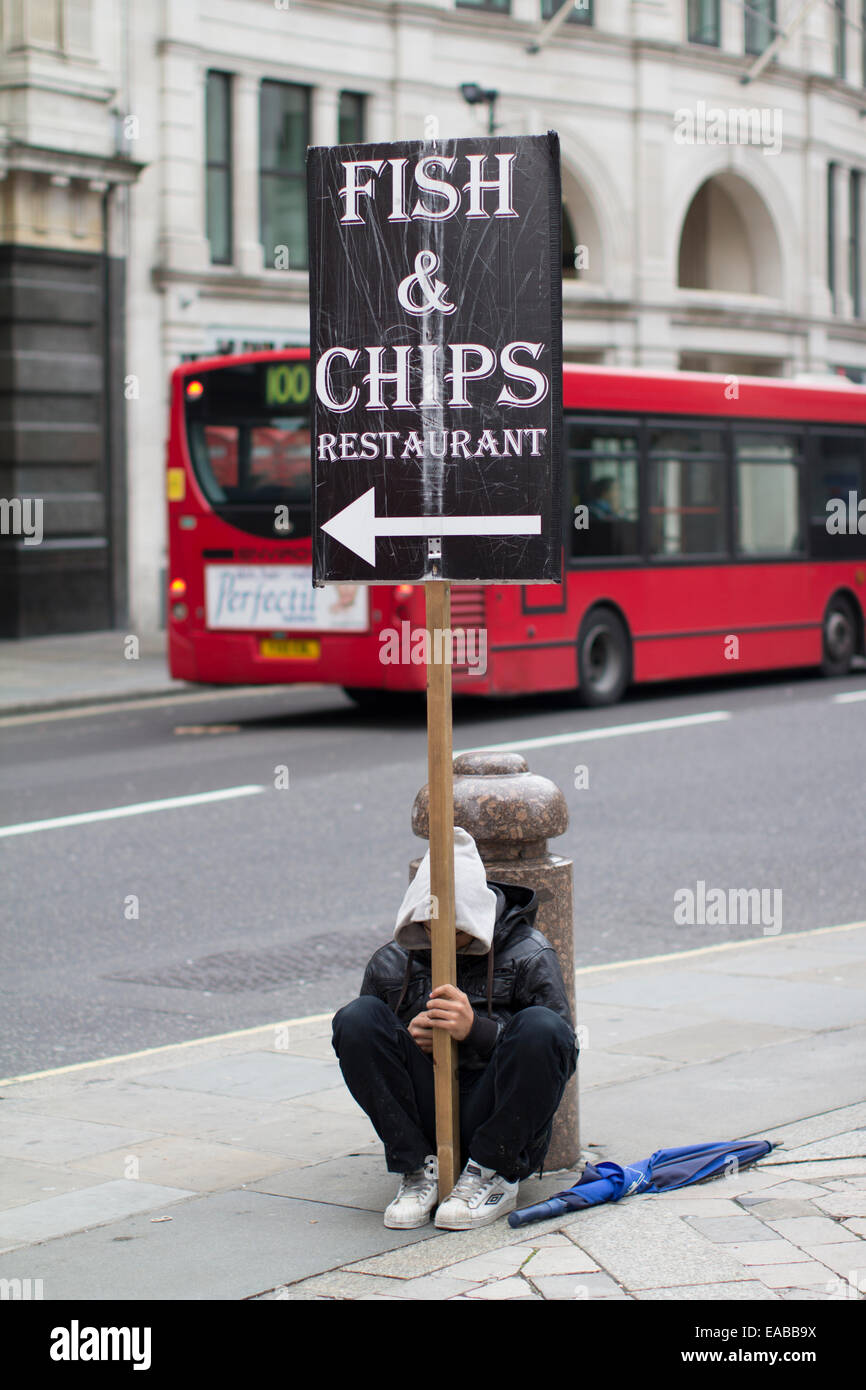 Bored Disaffected youth young male with Fish and chips sign - Stock Image