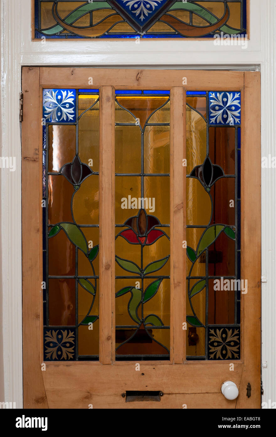 Stripped wooden door with stained glass panels in a Victorian terrace house. - Stock Image