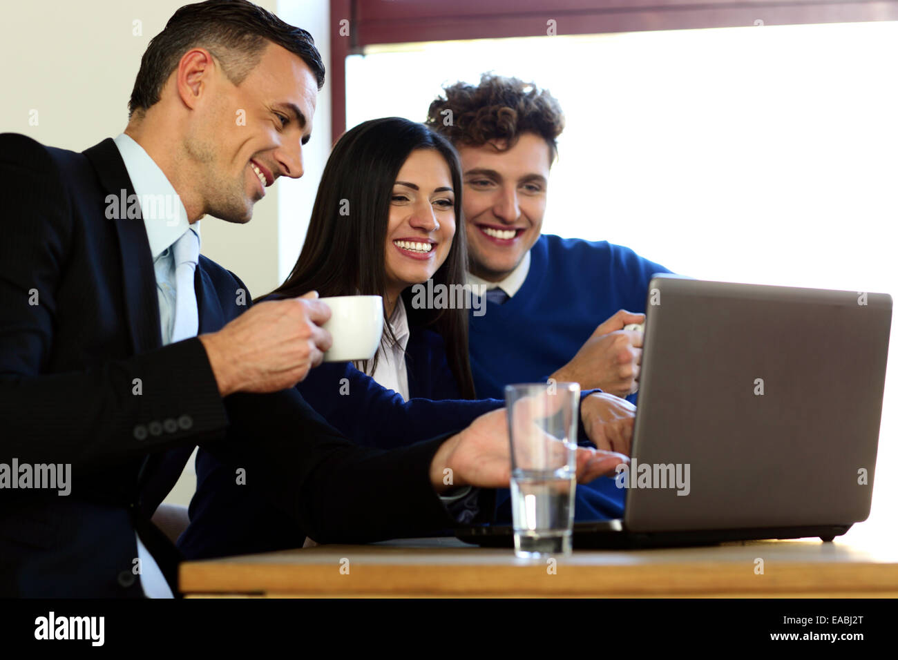 Business people using laptop together in office - Stock Image