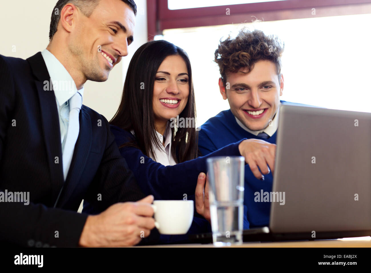 Smiling business people working on the laptop - Stock Image