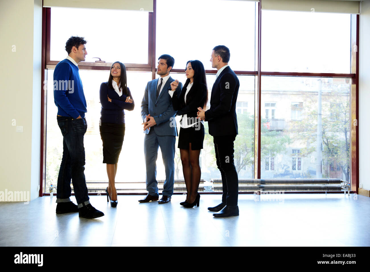 Full length portrait of a business people talking in the office - Stock Image