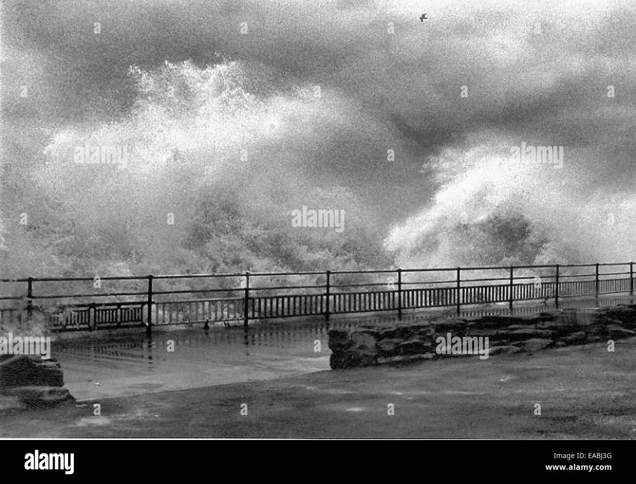 Large waves crashing against the lower promenade due to a storm at the coast in Whitley Bay, North East England. - Stock Image