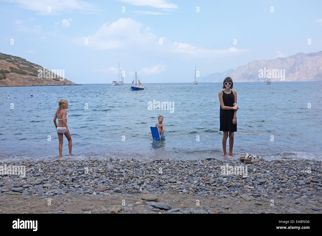 A teenage girl on holiday in Crete watched by two children - Stock Image