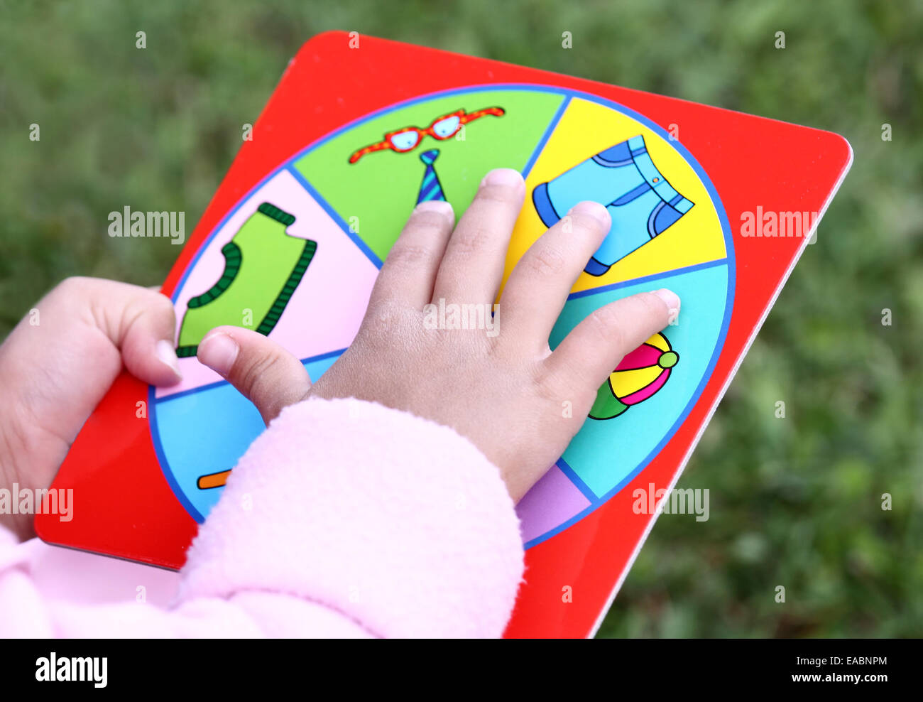 Little child hand holding board of learning game. Focus on hand and game table Stock Photo