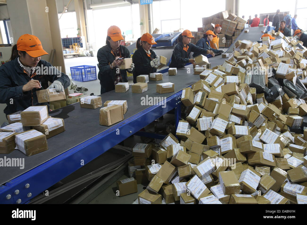 Xiangyang. 11th Nov, 2014. Workers sort out packages in a dispatching center of China Postal in Xiangyang, central - Stock Image