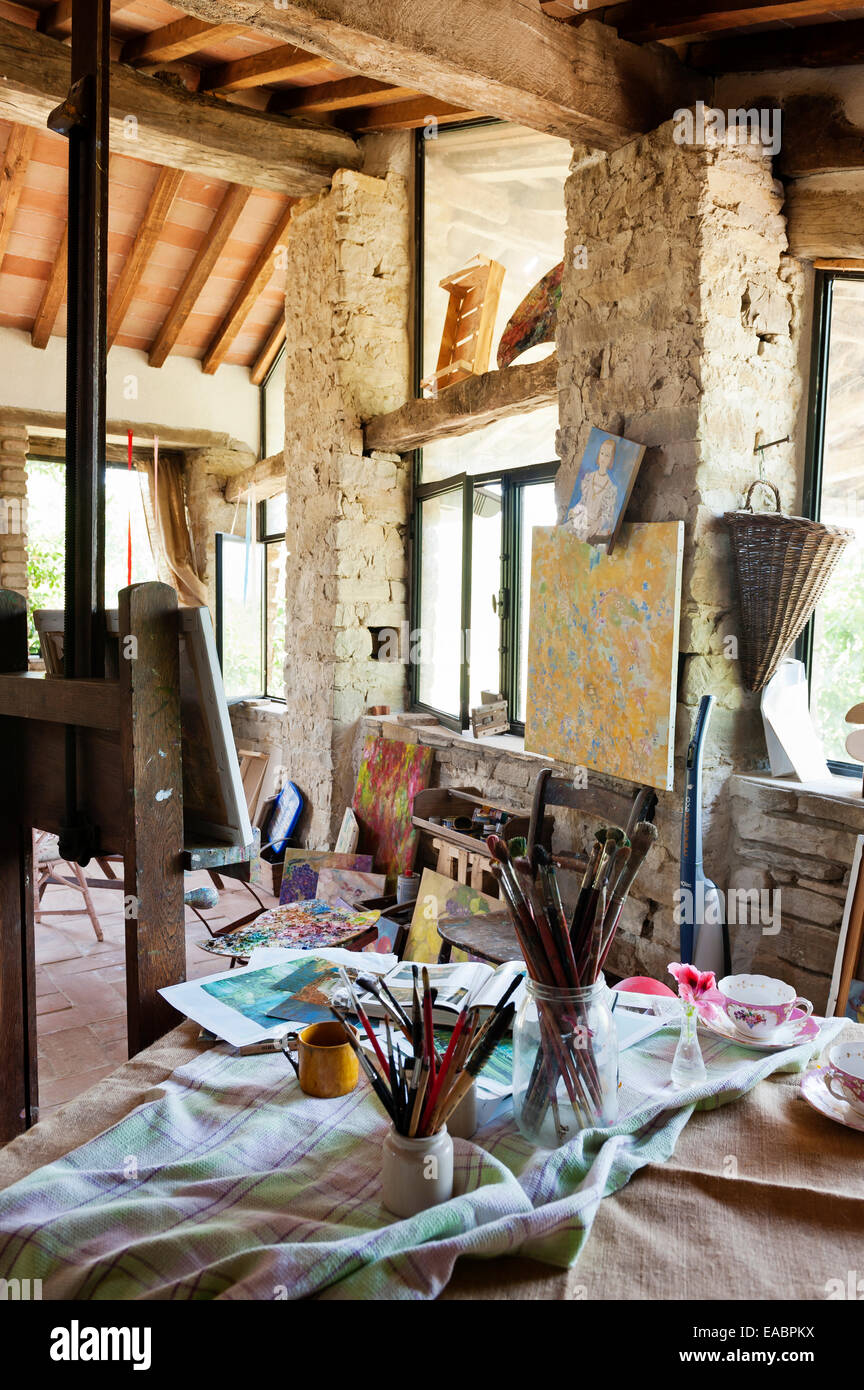 Jars filled with paint brushes in rustic artists studio - Stock Image