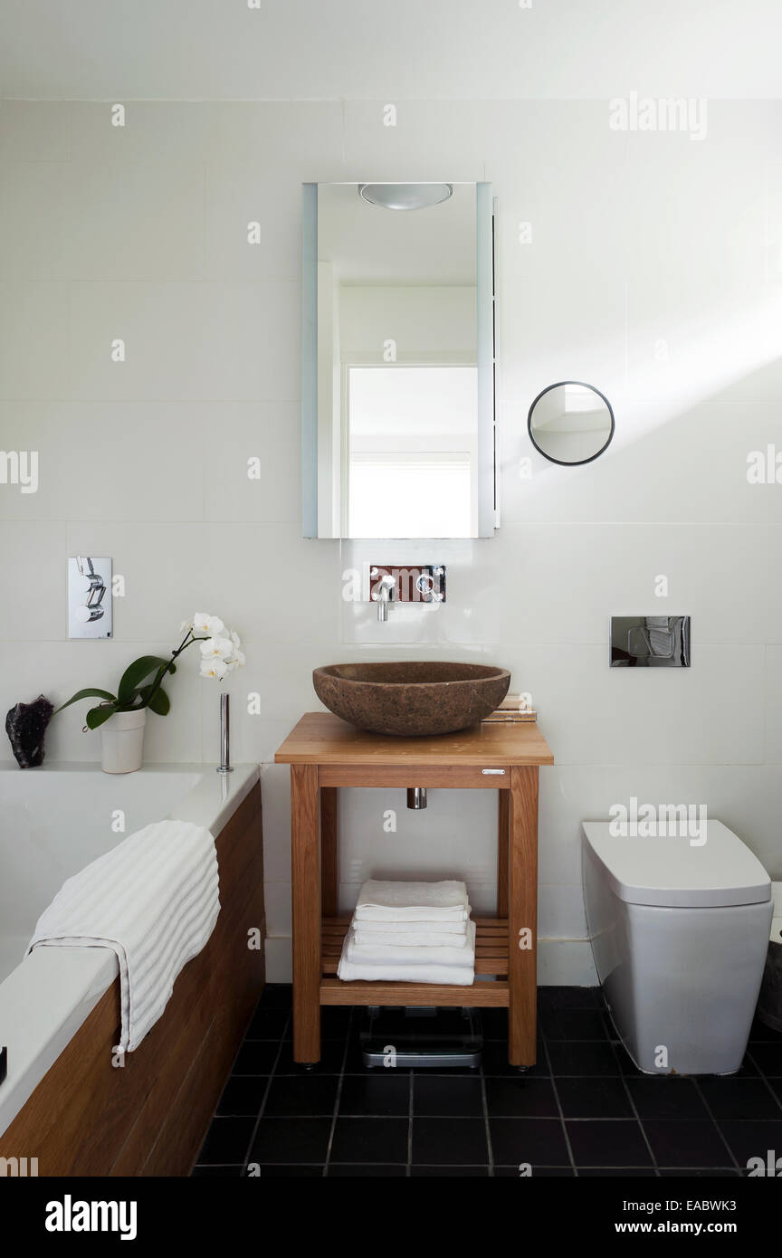 Stone bowl washbasin with wood stand in bathroom with slate floor ...