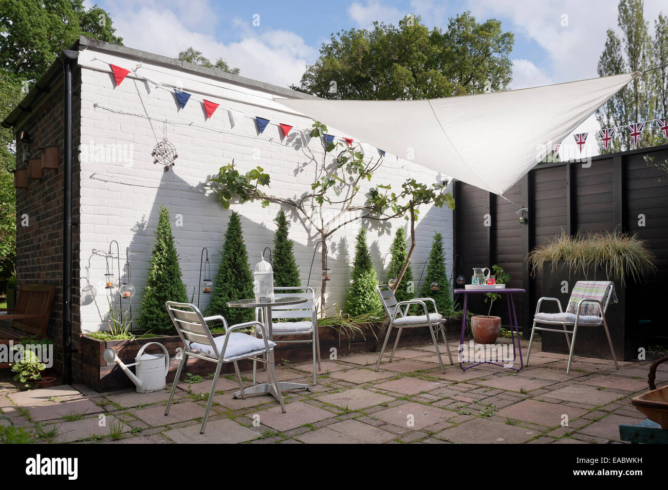 Chrome chairs and tables in paved garden with bunting and garden shade sail - Stock Image