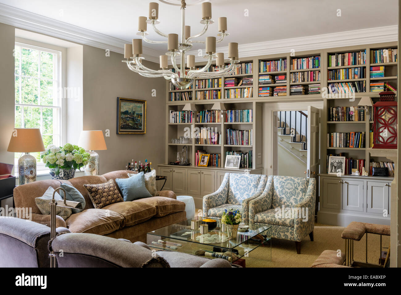 Murano chandelier and Kingscombe sofas and chairs in living room with inbuilt book shelves - Stock Image